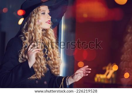 Happy shopping woman. Evening city - stock photo