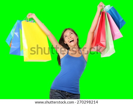 Happy shopping woman excited and cheerful in joyful bliss. Shopper holding colorful shopping bags isolated on green screen chroma key background. Elated beautiful Caucasian Asian Chinese female model. - stock photo