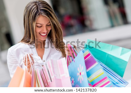 Happy shopping woman looking at purchases and smiling - stock photo