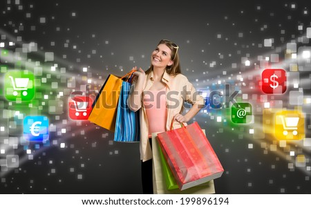 happy shopping woman surrounded by glow icons of e-commerce - stock photo