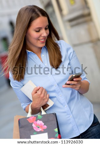 Happy shopping woman texting on her phone - stock photo