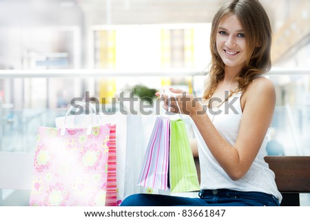 Happy shopping woman with bags and smiling. She is shopping inside mall