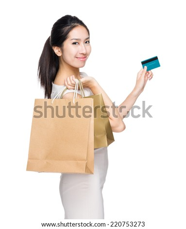 Happy shopping woman with paper bag and credit card