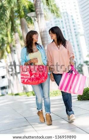 Happy shopping women walking in the streets of Miami with bags - stock photo