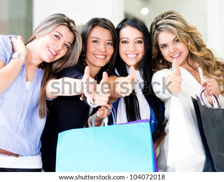 Happy shopping women with thumbs up and smiling - stock photo