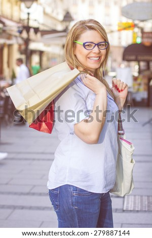 Happy Shopping Young Woman with bags on the street.Portrait caucasian female . - stock photo