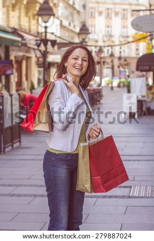Happy Shopping Young Woman with bags on the street.Portrait urban caucasian female . - stock photo