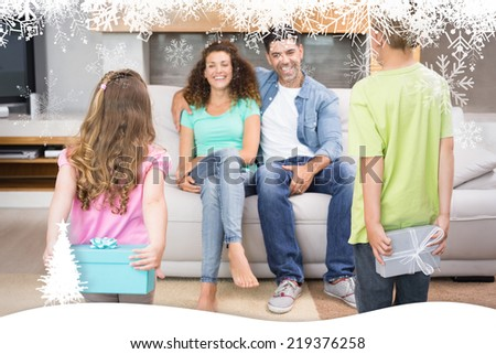 Happy siblings hiding presents behind their back from their parents against fir tree forest and snowflakes - stock photo