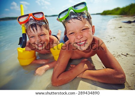 Happy siblings in goggles looking at camera on the beach - stock photo