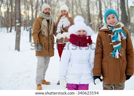 Happy siblings in winterwear looking at camera with parents on background - stock photo