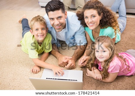 Happy siblings lying on the rug using laptop with their parents at home in living room - stock photo