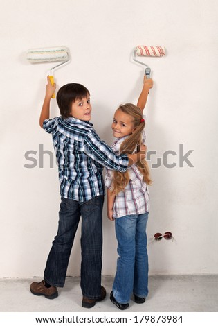 Happy siblings painting the room in their new home - using painting rollers - stock photo