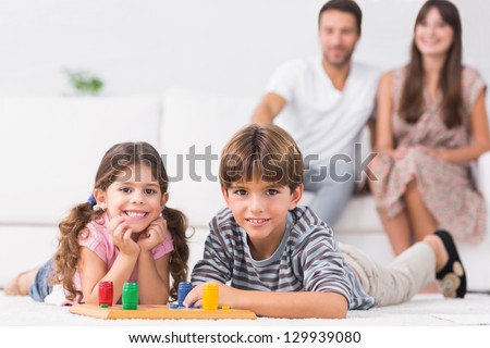 Happy siblings playing board game on floor with parents sitting behind them - stock photo