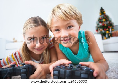 Happy siblings playing video games on floor at christmas time - stock photo