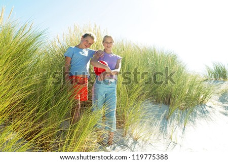 Happy siblings posing in the tall beach grass and soft white sand - stock photo