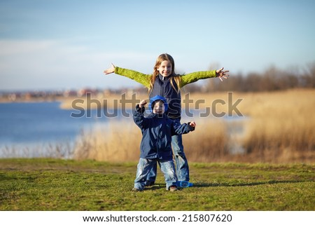 Happy sister and brother having fun beside the river. Happy lifestyle kids - stock photo