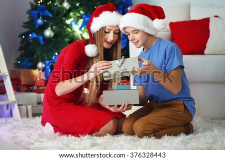 Happy sister and brother open gift box on the floor in decorated Christmas room