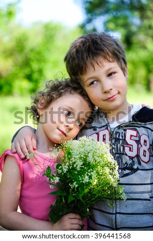 Happy sister and brother portrait together with flowers in the park at summer. Adorable, cute children, friends, kids outdoors. Lifestyle family concept. A boy and a girl are resting and having fun. - stock photo