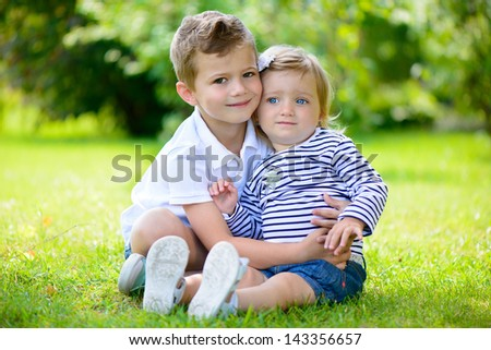 Happy sister and brother together in park during summer day