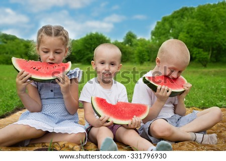 Happy sister and brothers eating watermelon.