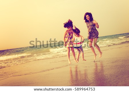 happy sister girls jumping at the beach