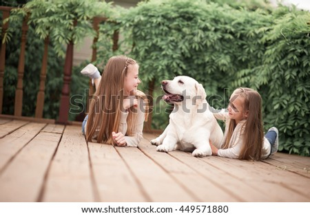 Happy sister girls playing with labrador outdoors. Playful. Togetherness. - stock photo