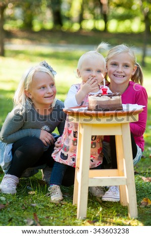 Happy sisters are smiling outside in the park. They are looking at camera and celebrating the first year of their little sister. - stock photo