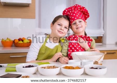 Happy sisters cooking together. Young happy children kids family having fun preparing granola in kitchen at home