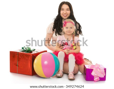 Happy sisters different ages together rejoice in the coming of the New year. Girls love to receive gifts - Isolated on white background.The concept of the celebration and the value of family - stock photo
