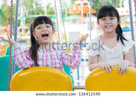 Happy sisters enjoying a weekend on a playground - stock photo