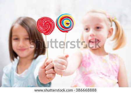 happy sisters have tasty lollipop