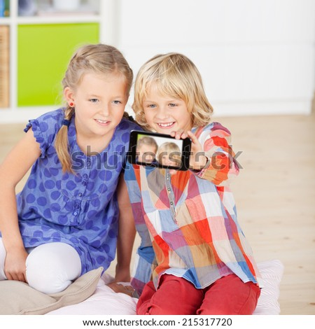 Happy sisters taking self portrait through mobile phone at home - stock photo