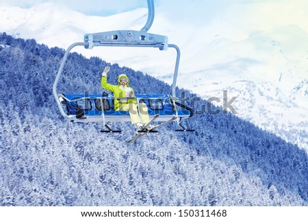 Happy skier young woman sit on the ski lift and waiving hand - stock photo