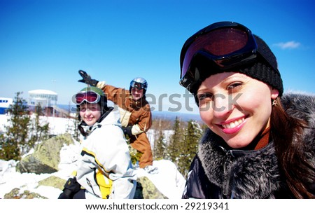 Happy skiers resting on the top of mountain
