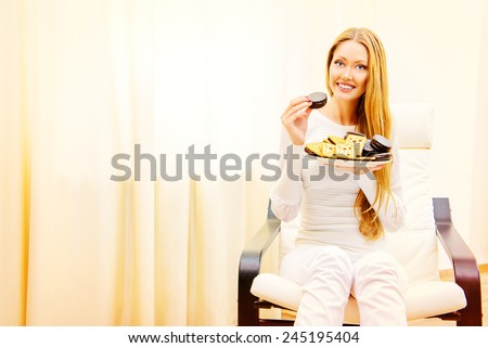 Happy slim girl with pleasure eats tasty cookies with chocolate. Healthy eating. Diet. - stock photo