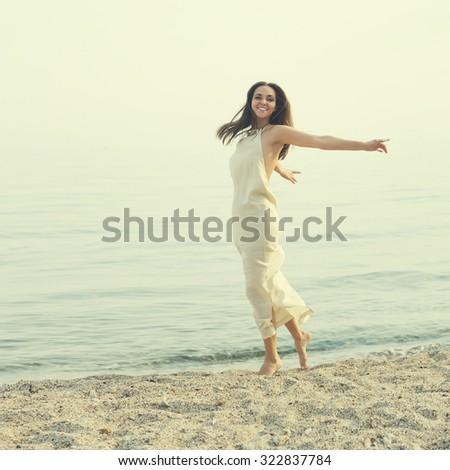 Happy slim woman dancing against sea landscape. - stock photo