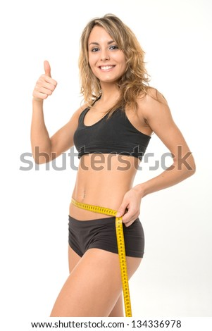 Happy slim woman measuring her waist - stock photo