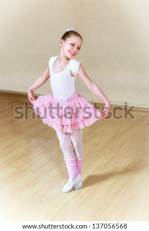 happy small ballerina at dancing school