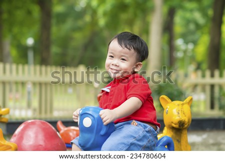 Happy small boy playing on playground. Summer park. Outdoors. - stock photo