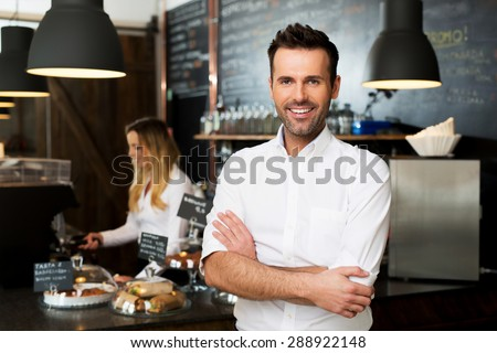 Happy small business owner standing at front of bar with employee in background preparing coffee - stock photo