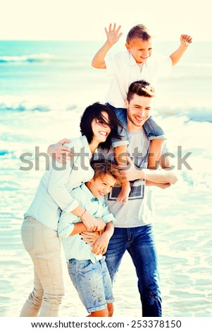 Happy Small Family Having a Vacation at the Beach During Summer. - stock photo