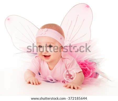 Happy small girl butterfly wings plays on the floor on a background - stock photo