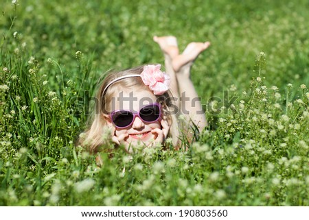 happy small girl in grass - stock photo