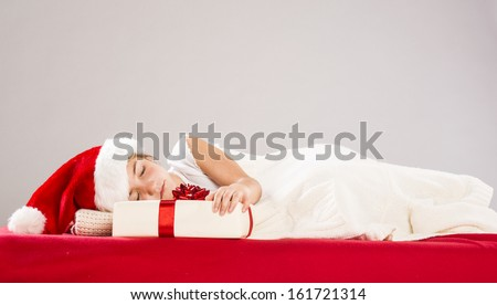 Happy small girl in santa hat with christmas gift, lying on the bed - stock photo