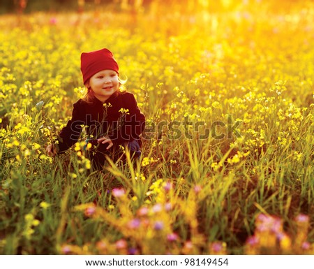happy small girl with field flowers - stock photo