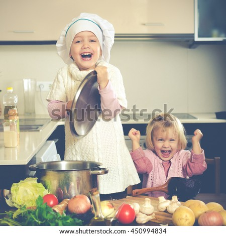 Happy small girlfriends try to cook vegetable soup in big pan indoor