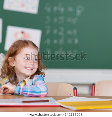 Happy small schoolgirl smiling in the classroom while sitting at the desk with a the chalkboard in the background - stock photo