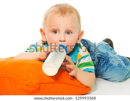 Happy smart blond boy drinking formula laying on pillow