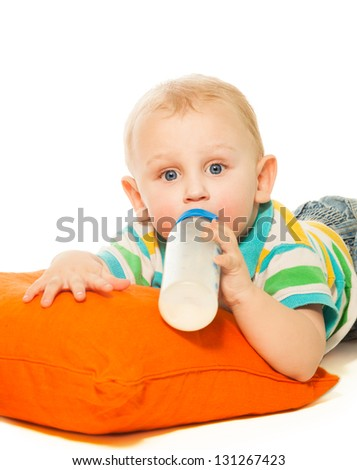 Happy smart blond boy toddler drinking formula laying on pillow