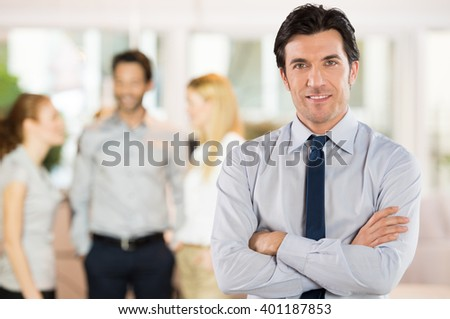 Happy smart businessman with team discussing in the background. Portrait of a handsome confident business man looking at camera. Successful manager at the office.